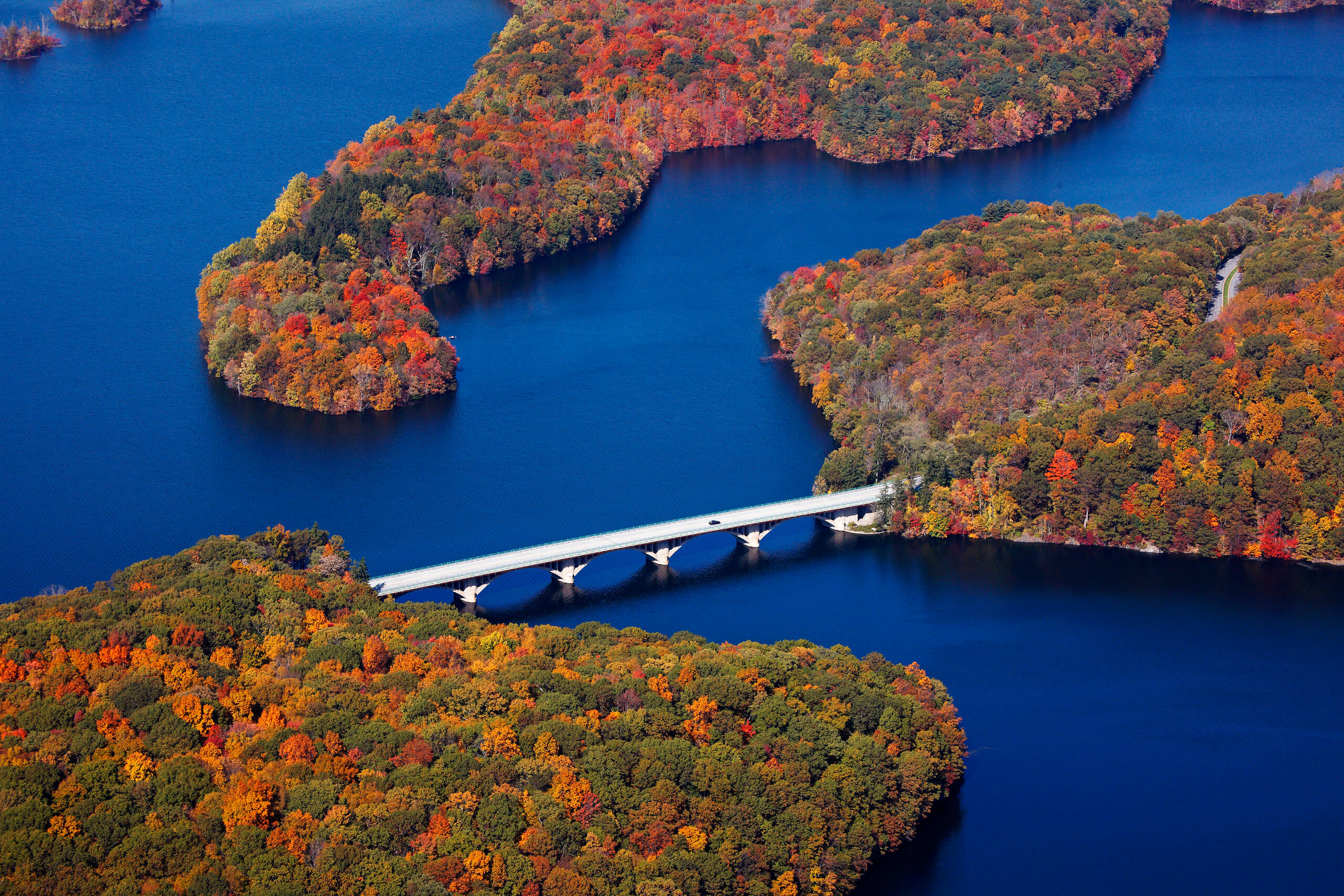Aerial photo of a highway bridge across Kensico Reservoir in Westchester County with fall foliage.