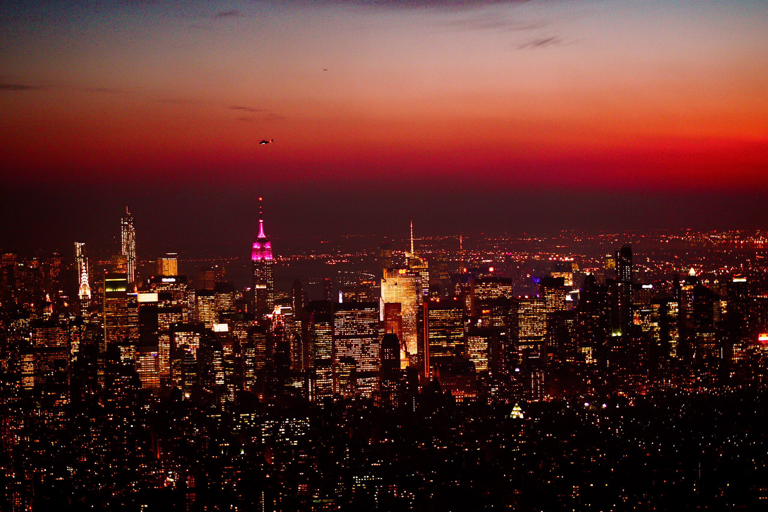 Aerial photo shot at night in New York City, NYC featuring the Empire State Building and Central Park